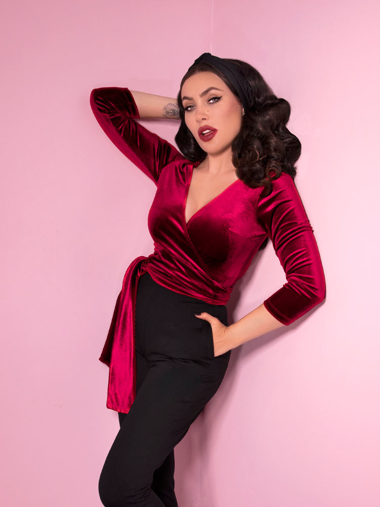 Micheline Pitt posing with one of her hands in her pockets and one placed behind her head, shows off her vintage inspired outfit featuring the Wrap Top in Raspberry Red.