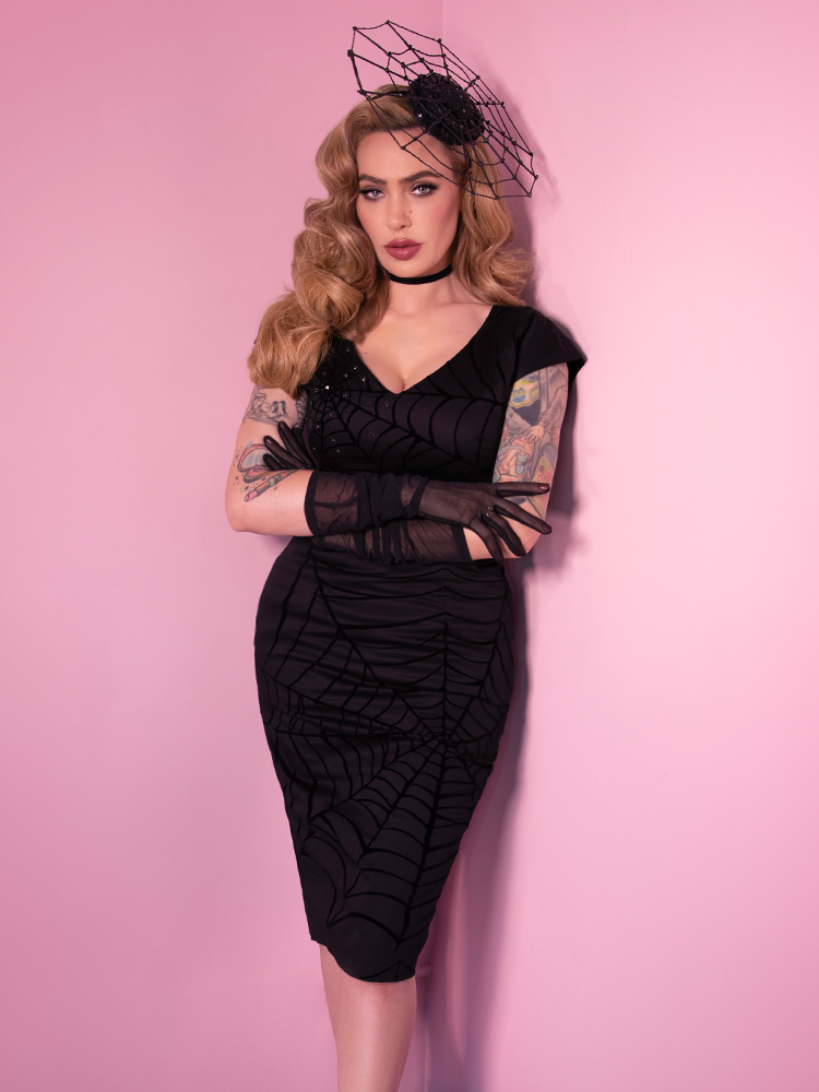 Micheline Pitt modeling a black retro inspired spiderweb dress with matching hat.