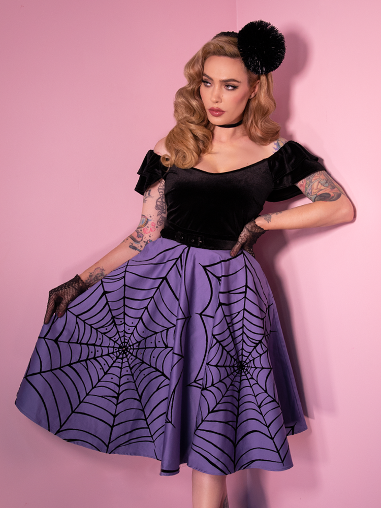 3/4 length shot of Micheline Pitt standing against pink walls while wearing a lavender colored skirt with spiderweb print and rhinestone embroidery, and a velvet retro style top.