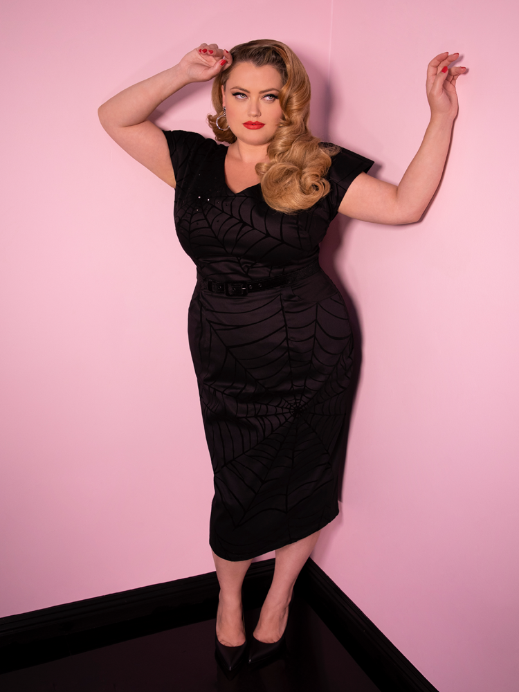 A full shot of Blondie with her hands up while modeling the Widow spiderweb dress in black by Vixen Clothing.