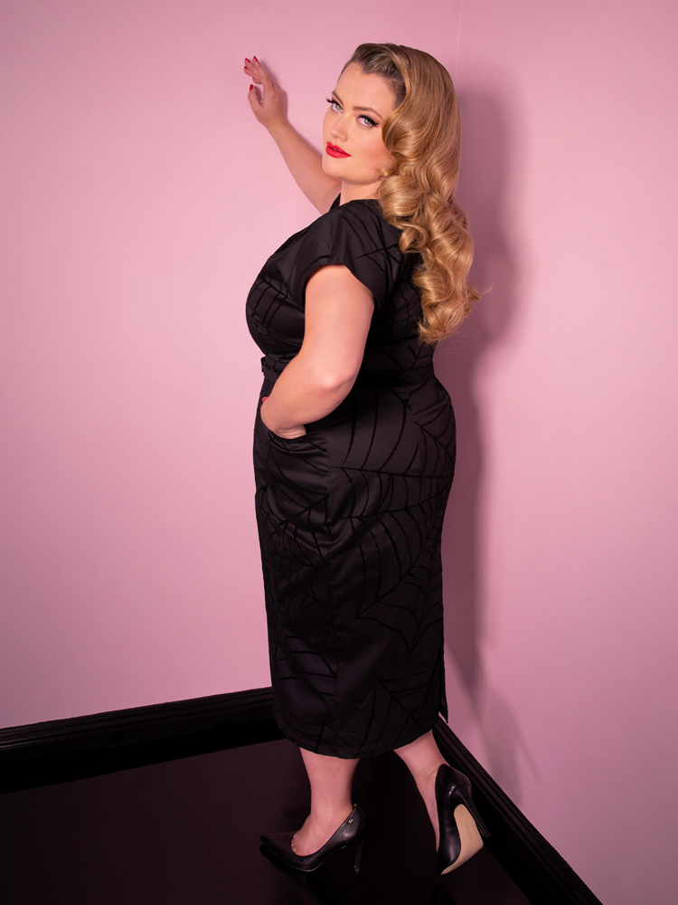 A side shot of Blondie looking at the camera while modeling the Widow spiderweb dress in black by Vixen Clothing.