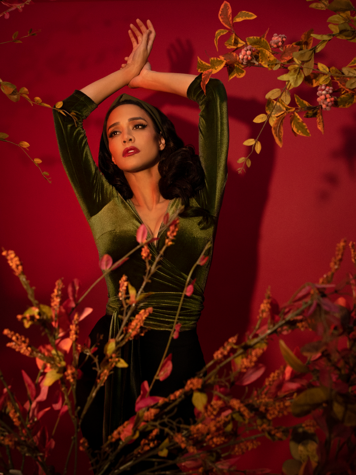 Milynn Moon poses against a dark red background with tree branches and leaves surrounding her while wearing the Wrap Top in Olive Green from Vixen Clothing.