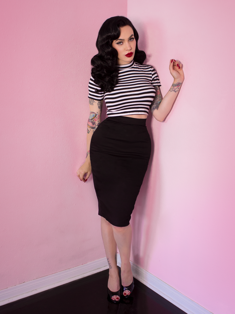 Full length shot of Micheline Pitt standing in the Bad Girl Crop Top in Black and White Stripes.