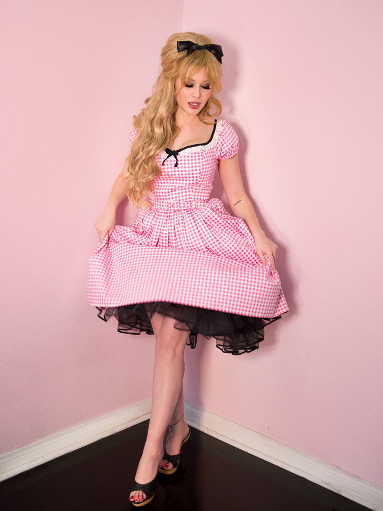 A model wearing the Bardot Beauty Dress in Pink Gingham while gently stretching out the bottom of the dress revealing a black ruffle petticoat.