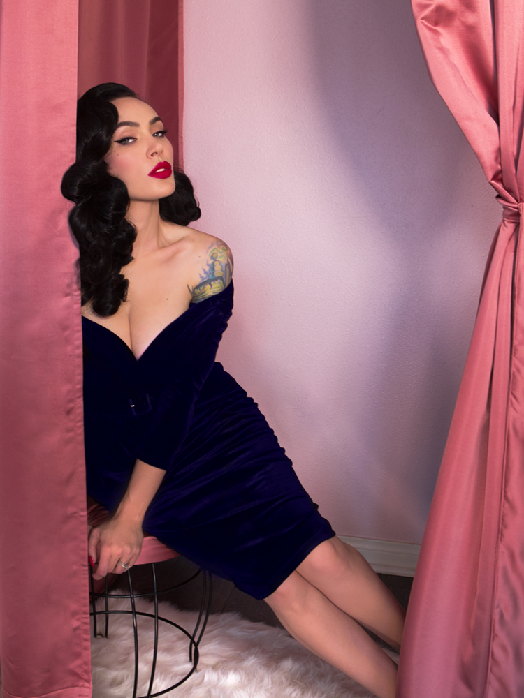 Micheline Pitt sitting on a pink stool while slightly leaning forward wears a retro inspired blue velvet dress from Vixen Clothing.