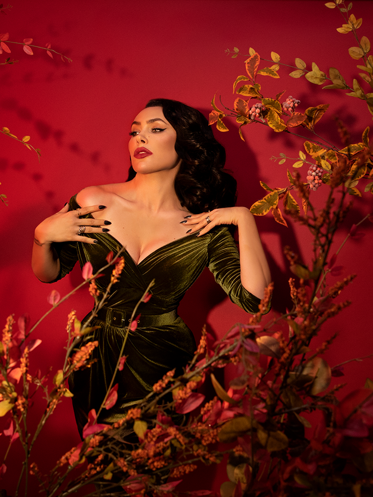 Stylized shot of Micheline Pitt in the Starlet Wiggle Dress in Olive Green posing in front of a blood red background and amongst yellow and green leaved branches.