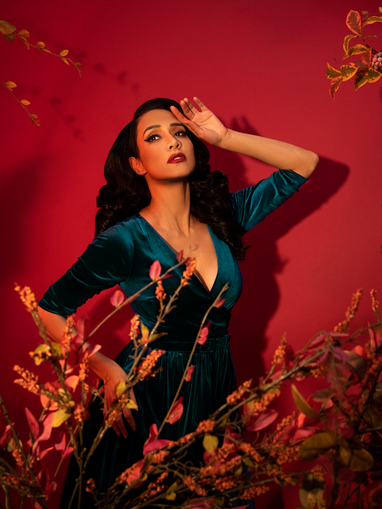 Milynn Moon looking like a damsel in distress in a red tinged forest themed shot while wearing the Allure Dress in Teal Velvet from Vixen Clothing.