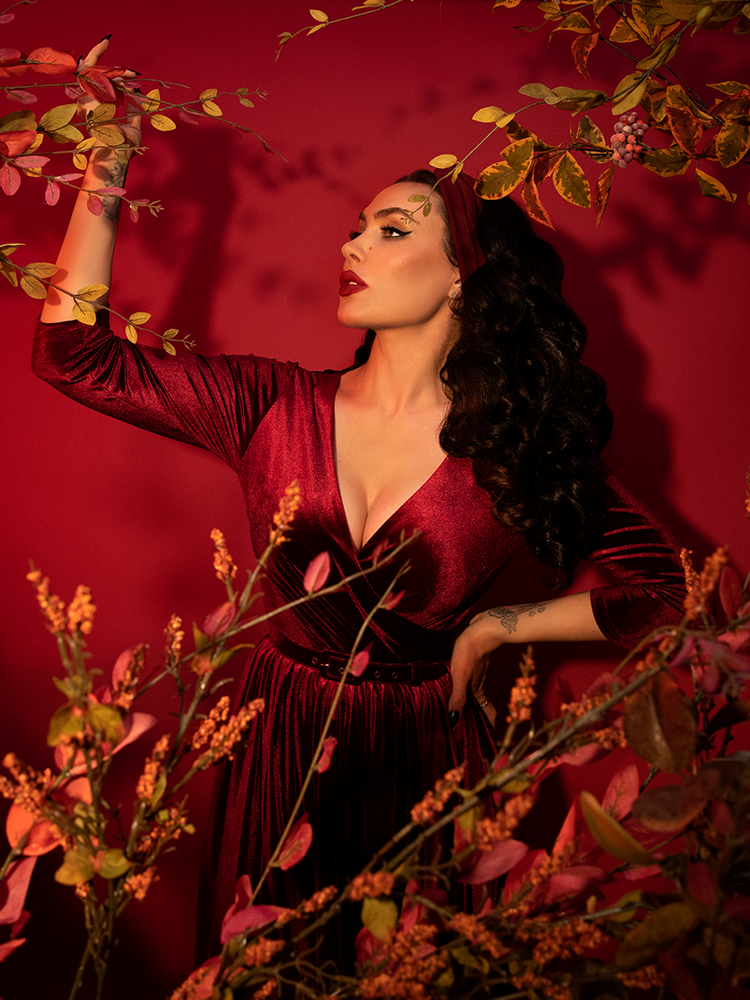 Shot against a red background and among forest branches and leaves, Micheline Pitt models the Allure Dress in Raspberry Red Velvet from Vixen Clothing.