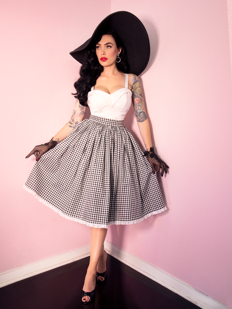 Wearing black lace gloves with a white and black gingham print skirt, Micheline Pitt sports the Maneater Top in White from Vixen Clothing which offers a wide array of retro inspired clothing pieces and accessories.