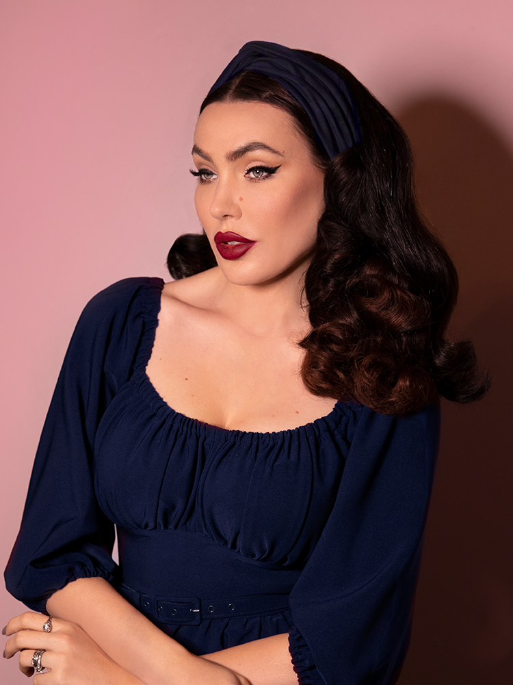 Looking off camera, Micheline Pitt wears a blue long sleeve top along with matching retro inspired knot headband in navy.