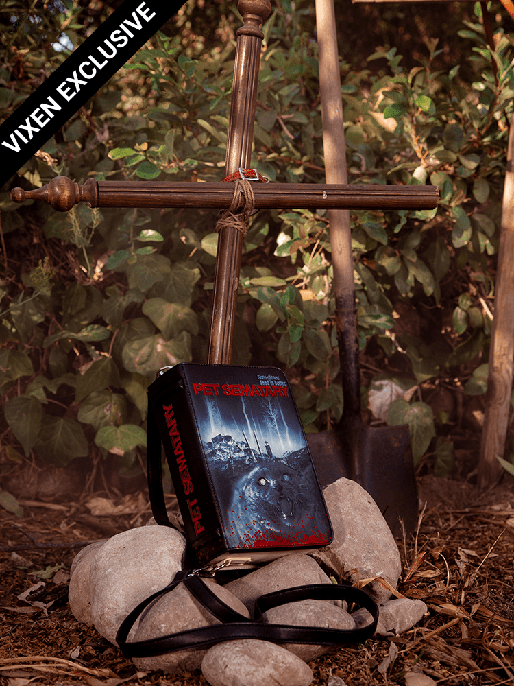 Pet Sematary book purse resting on top of a makeshift gave with large stones and cross fashioned from wood bedposts.