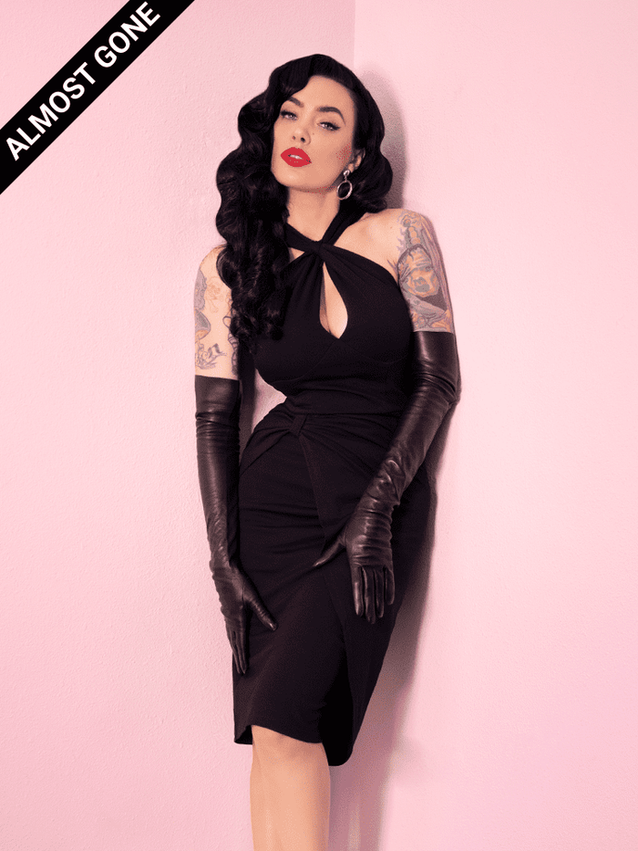 Wearing elbow-length black faux leather gloves, Micheline Pitt models the Golden Era Dress in black from Vixen Clothing.