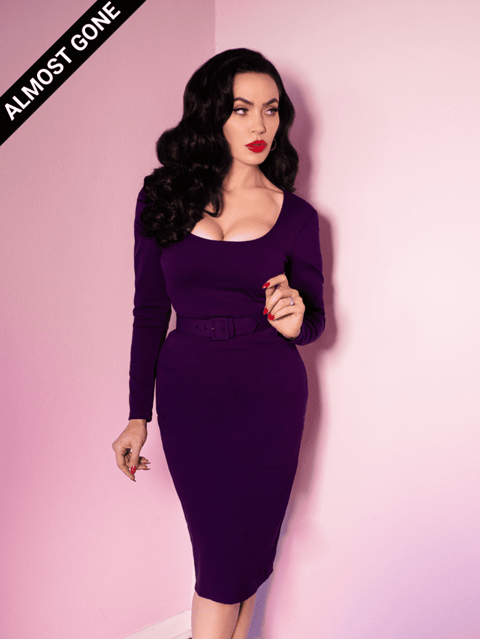 "Standing at the corner of two pink walls, Micheline Pitt looks off-camera while wearing the form fitting retro era dress called the ""Troublemaker Wiggle Dress in Purple"" from Vixen Clothing. It's a form-fitting rich purple dress with a low cut bust, belt from your waist and a cut that falls just below the knees."
