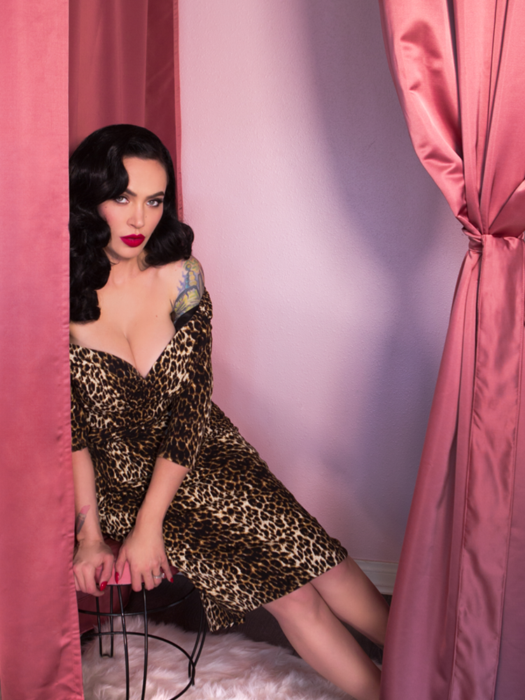 Sitting on a stool in a fitting room, Micheline Pitt models a starlet wiggle dress in leopard print.