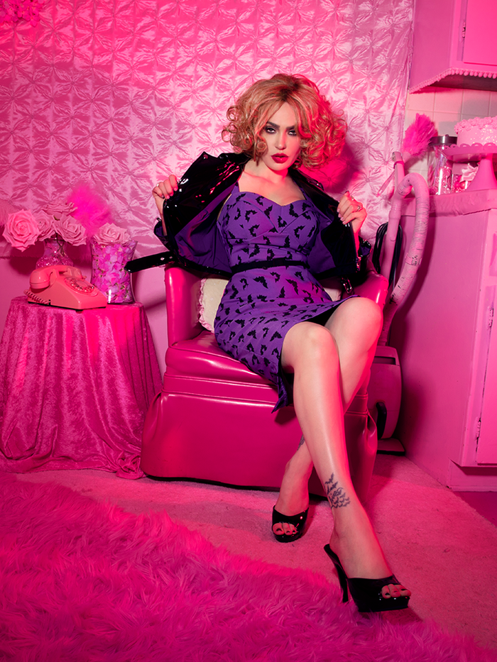 Micheline Pitt sat in an all pink room wearing the Miss Kitty Maneater Wiggle Dress in Bat Print.