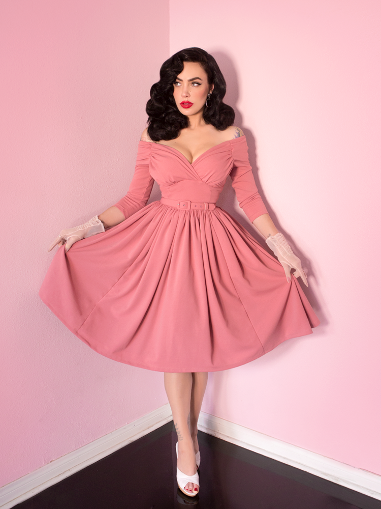 Micheline Pitt wearing a pink dress against a pink wall