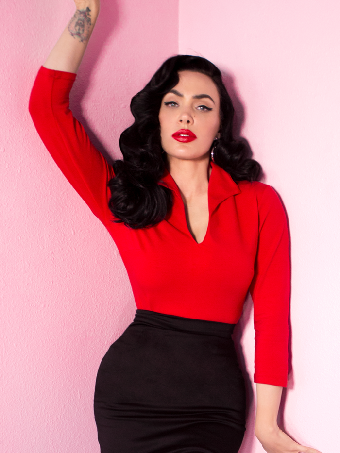 Micheline Pitt modeling the Vixen Top in Ravishing Red with a form fitting black pencil skirt.
