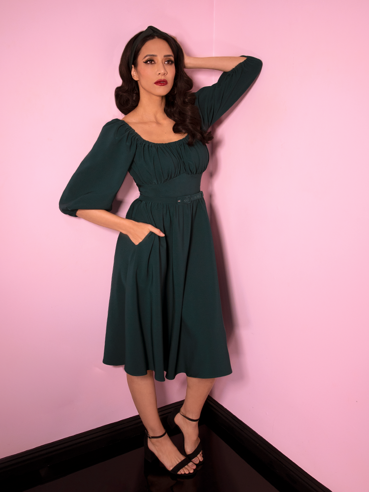 Full length shot of Milynn Moon with one hand in her pocket and one on her head wearing the Vacation Dress in Spruce Green from Vixen Clothing.