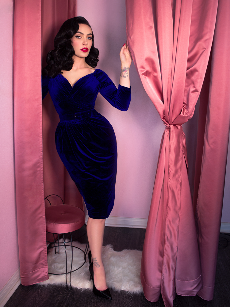 Slightly standing off-balance, Micheline Pitt places one hand on the curtain of a fitting room while looking directly into the camera while wearing a retro era velvet dress.