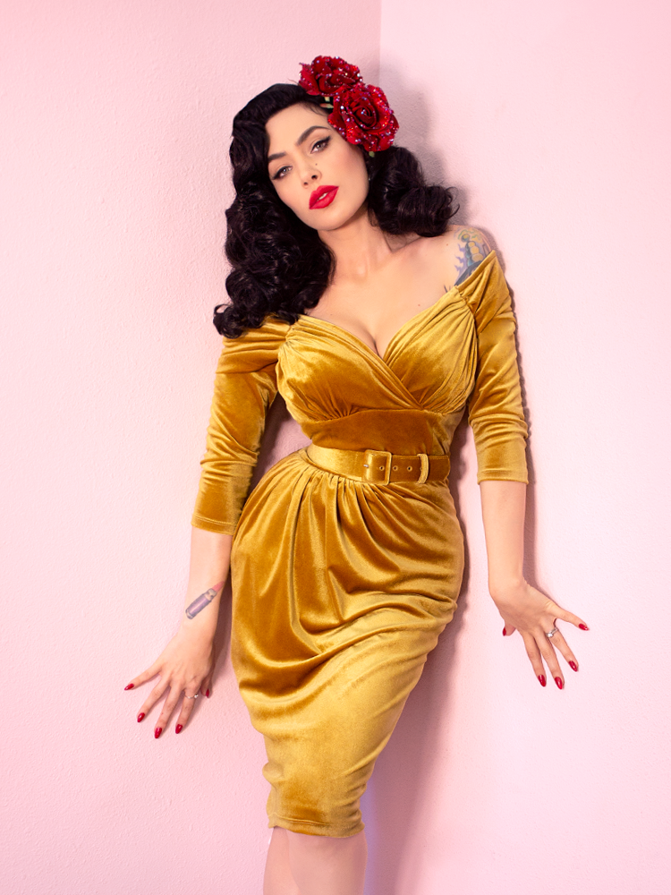Micheline Pitt wearing the Starlet Wiggle Dress in Gold Velvet with a faux floral headpiece tucked into her hair.