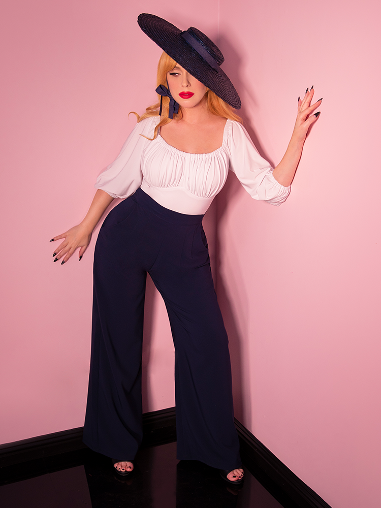 Wide shot of model wearing white retro blouse and blue wide leg pants.