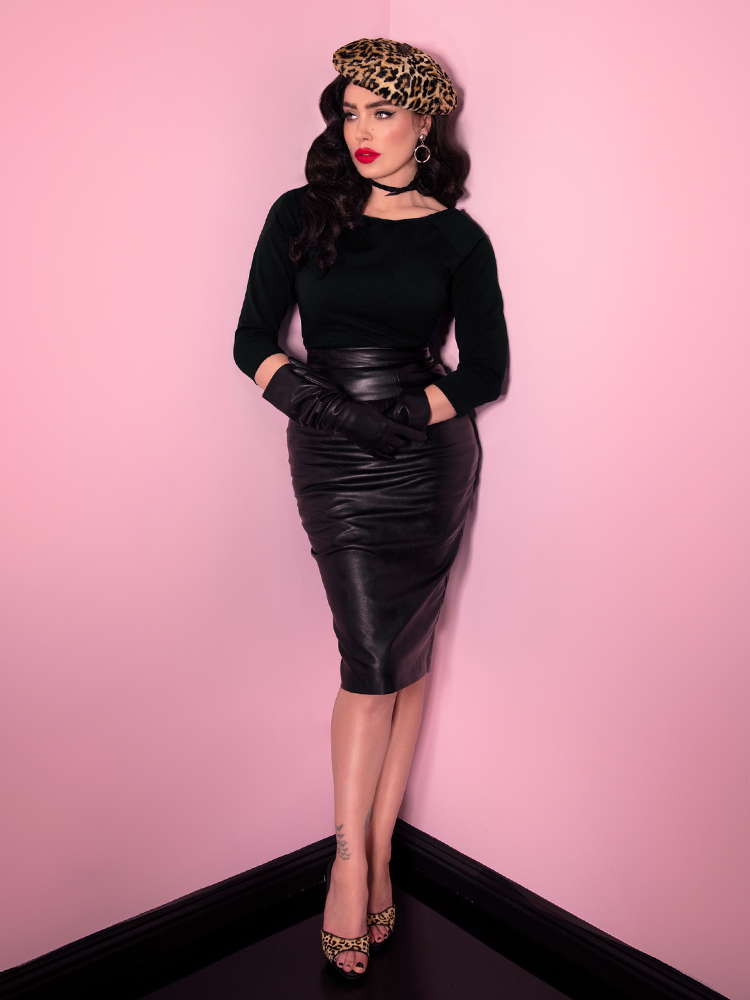 Full length shot of Micheline Pitt wearing a retro style outfit from Vixen Clothing including vegan leather pencil skirt, long sleeve black top and leopard print beret and shoes.