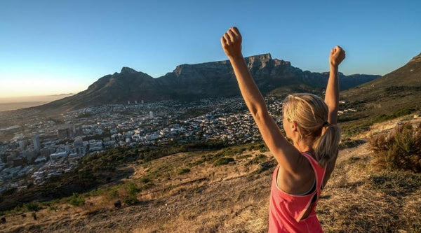 Woman runner on top of mountain with hands in the air