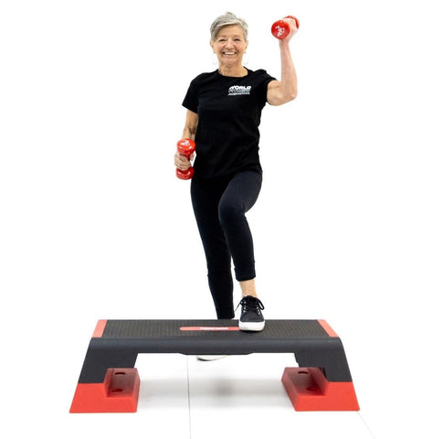 Woman posing with aerobic step & dumbbells