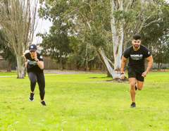 Man and woman sprinting side by side on grass