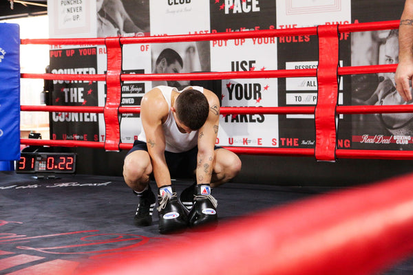 Man resting in boxing ring