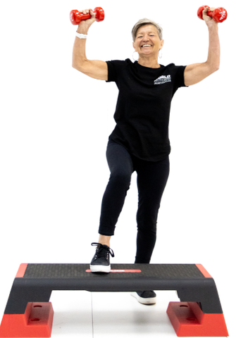 Lifestyle image of woman with aerobic step and dumbbells