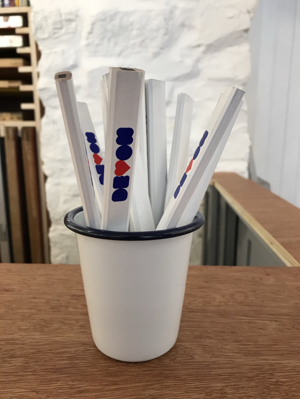 Carpenters pencils in a Falconware tumbler pot, on a desk in Salty's Studio - pencils have a graphic reading DEVON