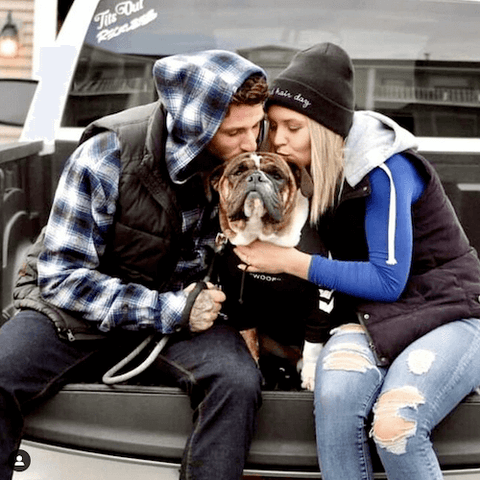 A Bulldog enjoying the company of his two humans while wearing the WOOF Dog Hoodie in Black and watching the world from the back of a pickup truck.