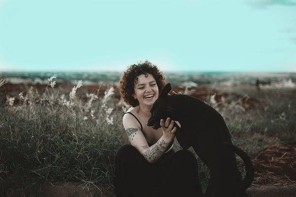 A woman enjoying her time with her black dog