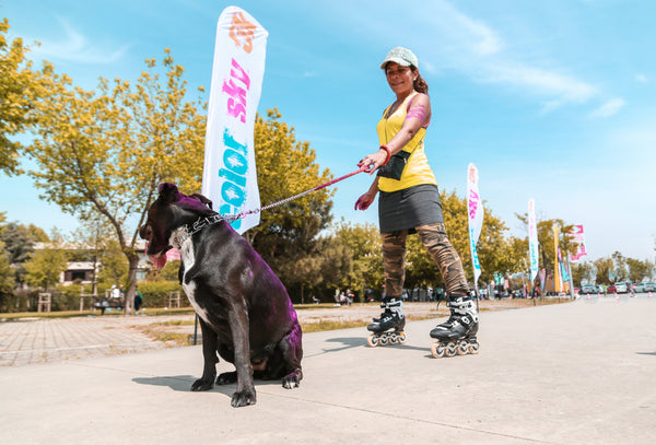 A woman rollerblading with her dog