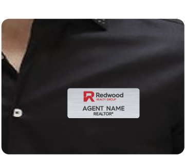 Name badge with Redwood Realty Group logo and agent name displayed on agent shirt