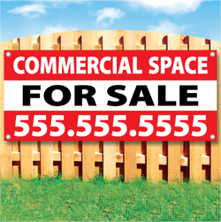 Wood fence displaying a banner saying 'COMMERCIAL SPACE' in white text on a red background and 'FOR SALE' in black Text on White Background
