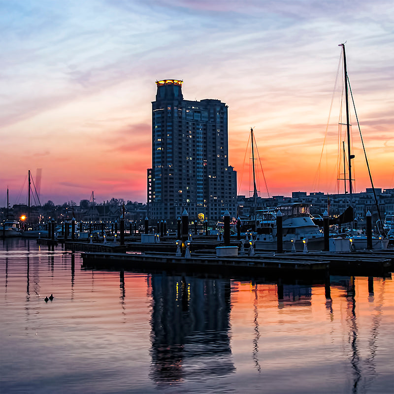 A colorful sky develops as the sun sets over the Baltimore harbor.