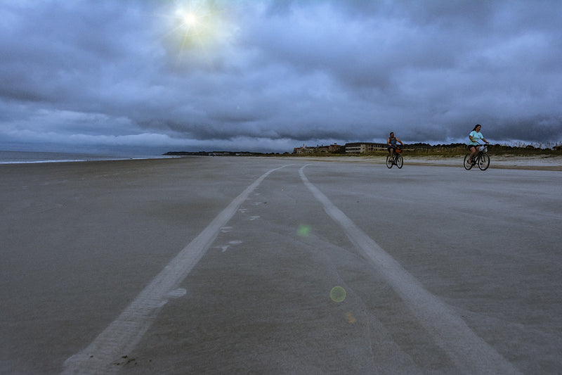 Bikers ride the beach on Hilton Head Island under an overcast but colorful sky.
