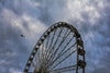 High in the sky, a jet plane passes above the Capital Wheel at National Harbor.