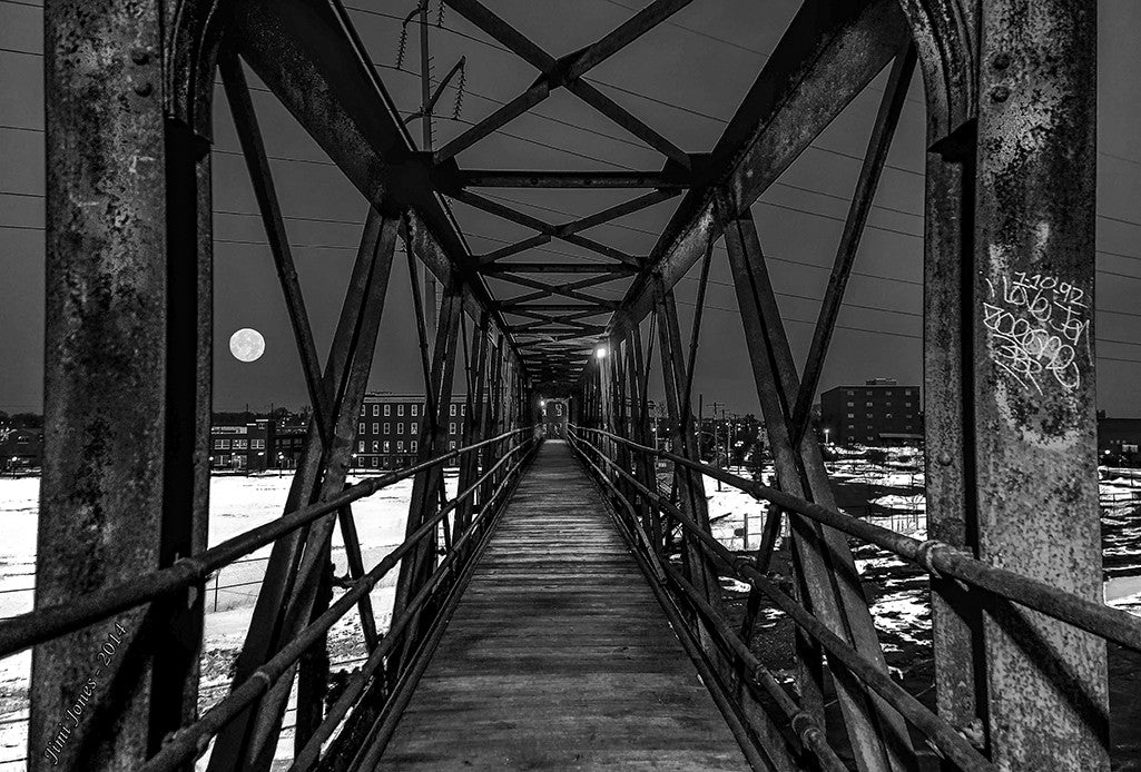 A full moon is framed by an elevated pedestrian walkway.