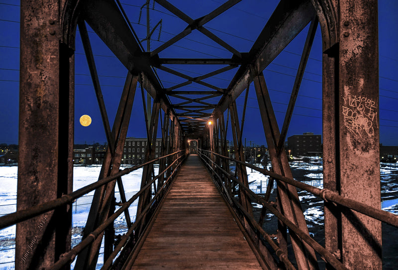 A full moon shine over a pedestrian bridge.