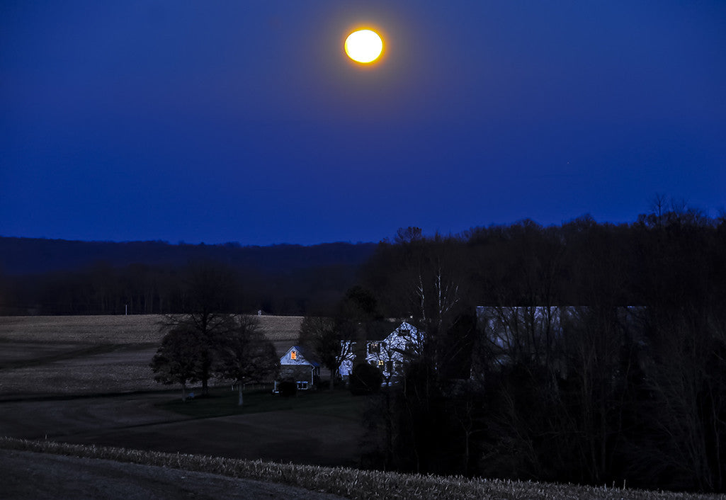 A rising moon shines brightly over a farm in Baltimore County.