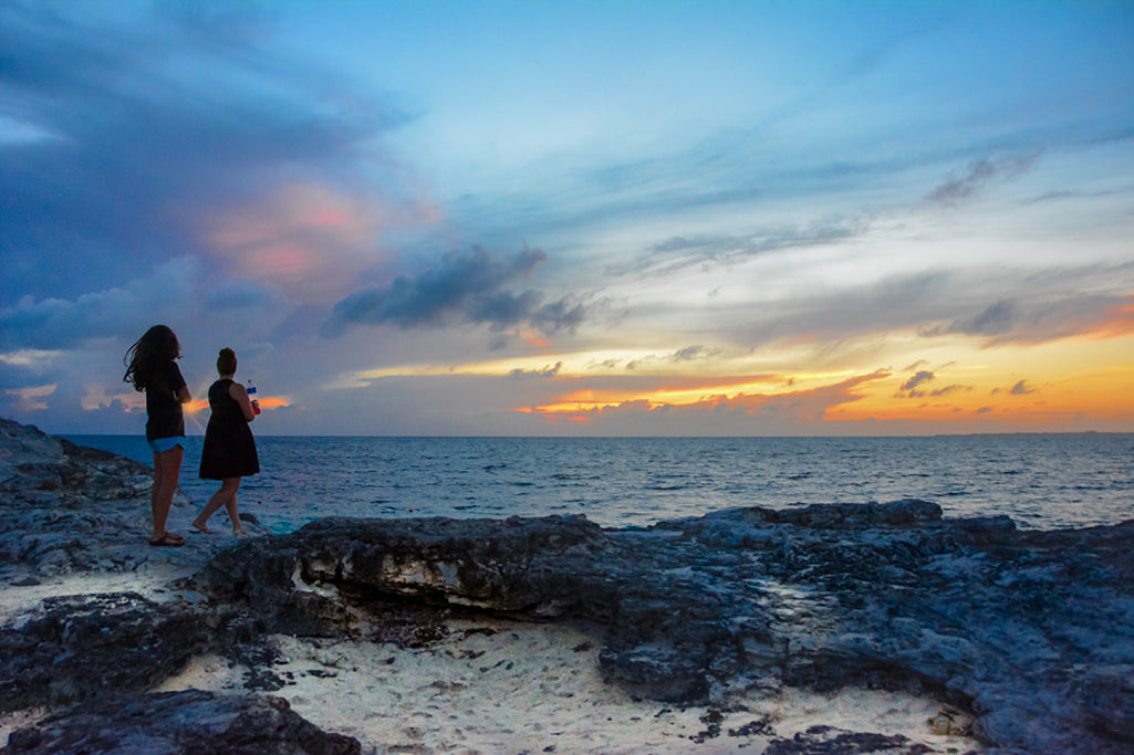 Ladies stand witness to Mother Nature's transitioning sky along the coast of the Caribbean Sea.