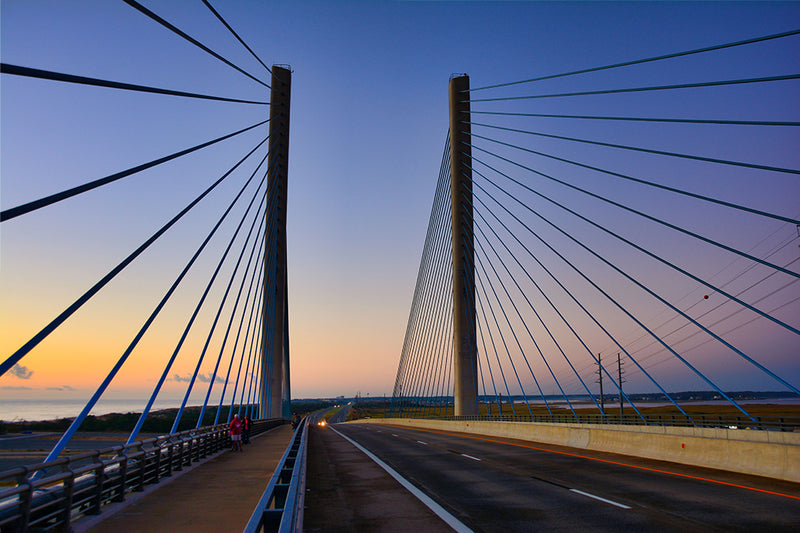 A beautiful sunrise sky adds beauty to this photograph of the Indian River Inlet Bridge in Dewey Beach, Delaware.