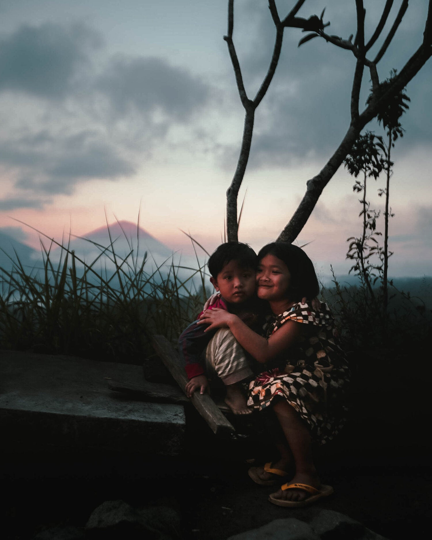 Two Balinese children smiling in front of Mount Agung, Bali