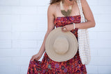 "Kirana WANDA 15"" large brim hat in Tan worn with KALANI flounce dress in Sangria & POPPY beaded tote in Natural"