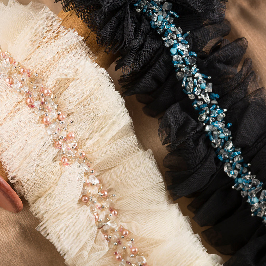 "This hand-crafted, beaded on soft raw-edged tulle trim is 4"" wide and sold by the yard for use on curtains, upholstery and home accessories. Perfect for the individual looking to achieve that luxurious, high-end look in their home, this trim by Michelle Workman for Pyar&Co. adapts perfectly to any room. Here our blush and black colorways are shown."