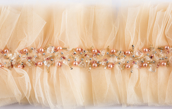 "This hand-crafted, beaded on soft raw-edged tulle trim is 4"" wide and sold by the yard for use on curtains, upholstery and home accessories. Perfect for the individual looking to achieve that luxurious, high-end look in their home, this trim by Michelle Workman for Pyar&Co. adapts perfectly to any room. This colorway is a soft, beautiful blush with pink and clear beading."