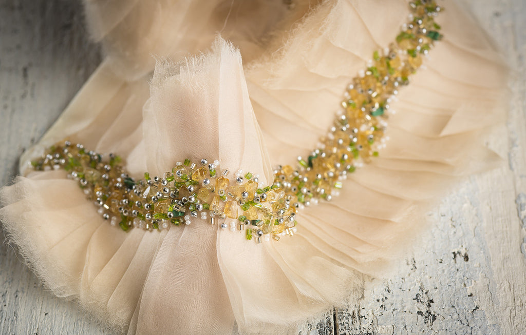 "This hand-crafted, beaded on soft raw-edged tulle trim is 4"" wide and sold by the yard for use on curtains, upholstery and home accessories. Perfect for the individual looking to achieve that luxurious, high-end look in their home, this trim by Michelle Workman for Pyar&Co. adapts perfectly to any room. This colorway is a soft, beautiful blush with green and yellow beading."